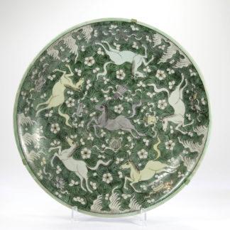Große Platte, 18./19. Jh., verziert mit der Darstellung der 8 Pferde des Kaisers Mu Wang in grün und ocker, umgeben von taoistischen Symbolen, zwei große Ausbrüche geklebt und alt restauriert. D: 37 cm, www.beyreuther.de