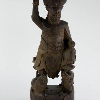 Figur, China, wohl Ming Dynastie (1368 bis 1644), Holz, geschnitzt, Tempelfigur, Wächter, auf Löwen und Drachen stehend, ursprünglich farblich gefasst und bemalt, schöne Ausarbeitung, Fehlstellen, auf modernen Steinsockel montiert. H: 43,5 cm, www.beyreuther.de