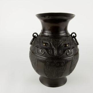 Archaisches Weingefäß, China, 18. Jh., oder älter, LEI Form, mit zwei großen TAOTIE Masken und 6 weiteren kleinen Masken auf der unteren Hälfte, mit Gold und Silber eingelegt, feine, gewachsene Patina, alter, defekter Einsatz aus Zinnblech. H: 27 cm.