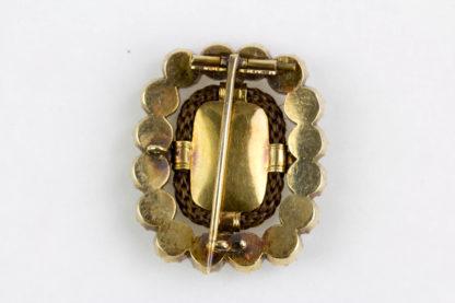 Brosche, England, viktorianisch, 14 Karat Gold, oval besetzt mit Burmarubinen- und Süßwasserperlenring, dazwischen geflochtenes Haar, sehr feine Qualität, Tragespuren. H: 2,7 cm, B: 2,4 cm.