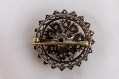Brosche, Mitte 19. Jh., Gold mit Silber aufgelegt, verziert mit Brillanten in Altschliff, in Mitte grüner Stein, wohl später, 4 kleine Brillanten fehlen. D: 3 cm, Gewicht: 11 g.