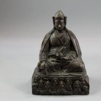 """Padmasambhava, Nepal, 18. Jh., Bronze, Padmasambhava (übersetzt: Lotosgeborener, auch Guru Rinpoche, gilt als Begründer des Buddhismus in Tibet zur Zeit des Königs Thrisong Detsen), im Lotossitz mit dicker Robe und einer Schale in der einen Hand, und einer Myrobalan Frucht in der anderen Hand sitzend Haare dreigeteilt über den Schultern und den Rücken fallend, eine Pandita als Kopfbedeckung, Sockel mit den """"Acht Manifestationen Padmamasambhavas""""mit Heiligenschein und Mandorlas umgeben, verziert, schöne, gewachsene Patina, Reste von roter Farbe am Sockel, Sockelabdeckung fehlt. H: 15 cm, A bronze figure of Padmasambhava, Nepal, 18th century, seated on a lotus base and wearing thick robes, jewelry and a Pandita cap, his hair flowing over his shoulders and back, holding a bowl in his left hand and a myrobalan fruit in his right, the Eight Medicine Buddha Brothers backed by halos and mandorlas, www.beyreuther.de"""