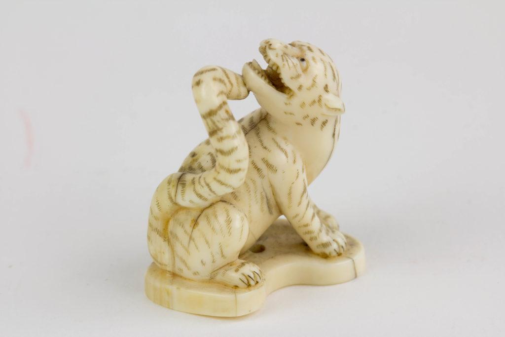 Netsuke, Japan, Meiji-Zeit, Bein, Tiger, geschnitzt und geschwärzt, signiert. H. 3,5 cm, www.beyreuther.de