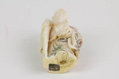 Netsuke, Japan, Anf. 20. Jh., Bein, Chokwaro mit Kürbisflasche auf Schulter, farbig abgesetzt, signiert, Gebrauchsspuren, H: 6 cm.