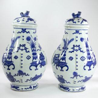 Paar Vasen, China, 19./20. Jh., Hu-Form, verziert mit buddhistischen Symbolen und kleinen Tischen mit Vasen und Blumen, in Blaumalerei, Deckelabschluß als Fo-Hund, Glasurfehler, Gebrauchsspuren, unbeschädigt. H: 37 cm, www.beyreuther.de