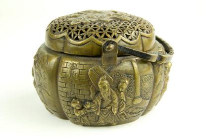 Handwärmer, China, 19./20. Jh., Ming Marke, Bronze, in vier Kartuschen Darstellungen von Glücksgöttern, Deckel durchbrochen gearbeitet, guter Zustand. H: 9cm, D: 13 cm.