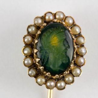 Krawattennadel, Niederlande, um 1870, Eichenblatt-Punze für 585er Gold, mittig grüner Stein mit geschnittenen antiken Portrait, von kleinen Flussperlen flankiert, sehr schöne Juwelierarbeit. L: 7 cm. www.beyreuther.de