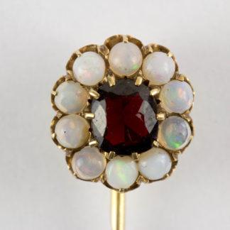 Krawattennadel, Ende 19. Jh., Gold, gemarkt Fuchs 4, mittig geschliffener Granat, flankiert von kleinen Opalen, schöne Juwelierarbeit. L: 7 cm. www.beyreuther.de