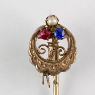 Krawattennadel, Ende 19. Jh., 585er Gold, und Silber, ungemarkt, halbmondförmig, graviert mittig Kleeblatt, mit Rubin, Perle und Saphir besetzt. L: 6 cm. www.beyreuther.de