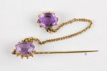 Krawattennadel, um 1900, 585er Gold ungemarkt, bestehend aus zwei gefassten Amethysten, die mit einem Kettchen verbunden sind, eine Nadel fehlt, sehr dekorativ. L: 4,5 cm.