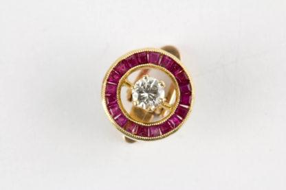 Clip, 20er Jahre, 750er Gold, ungestempelt, in Form eines Ringes, mit Rubin-Karree besetzt, mittig ein Brilliant von 0,20 ct, hochwertige Arbeit, Gebrauchsspuren. D: 11 mm. www.beyreuther.de