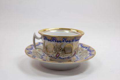 Tasse und Untertasse, um 1840, Biedermeier, wohl Schlesien, verziert mit feiner Ornamentmalerei in Gold, Blau und Rot, Untertasse leicht berieben, unbeschädigt. H: 7,5 cm.