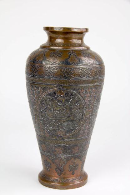 Vase, Syrien/Ägypten, Cairoware, Mitte 20. Jh., Kupfer mit Silber aufgelegt, umlaufend mit Ornamenten und Symbolen verziert, Gebrauchsspuren. H: 21 cm.