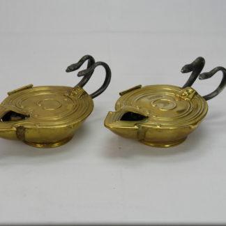 Paar Öllampen, um 1900, im Antiken Stil, Messing, Griffe als Schlangen aus Eisen, beim Zusammendrücken der Schlangen entzündet sich der Docht, Mechanik zu überholen, selten und originell. B: 7 cm, H: 10 cm, L. 17 cm. www.beyreuther.de