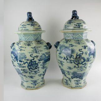 Paar Vasen, China, Mitte 20. Jh., umlaufend mit Fo-Hunden und Ornamenten in Blaumalerei verziert, Handhaben in Form von Löwenköpfen, Deckelbekrönung als plastische Fo-Hunde gearbeitet, sehr dekorativ, unbeschädigt, Gebrauchsspuren. H: 68 cm, D: 36 cm.