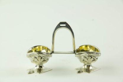 Salière, um 1900, 800er Silber gestempelt, in Form von zwei Ulanen Tschapkas, mit Steigbügel verbunden, innen vergoldet, ausgefallen, B: 11 cm, H: 7,5 cm. www.beyreuther.de